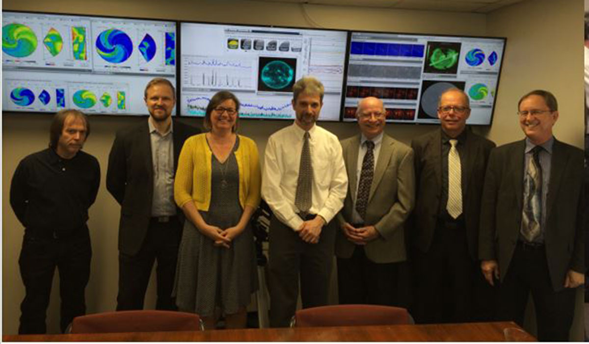 Faculty of the Space Weather Lab stand in front of monitors depicting space weather